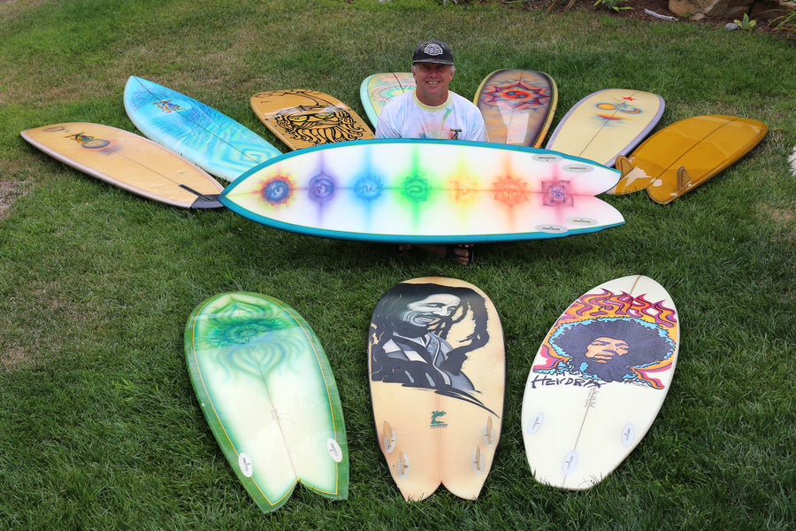 John Frazier sitting with his collection of Rainbow Surfboards