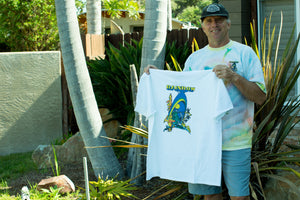 John Frazier standing with his white Rainbow Surfboards t-shirt