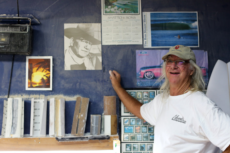 Gary Hanel in his surfboard shaping room looking at a picture of John Wayne