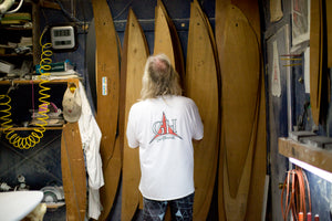 Gary Hanel standing in his surfboard shaping room looking at surfboard templates