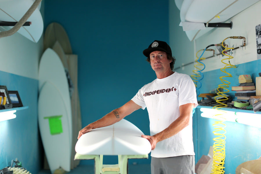 Chris Christenson standing in his surfboard shaping room