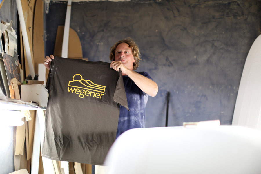 John Wegener standing in his surfboard shaping room holding his Wegener Surfboards brown surf t-shirt