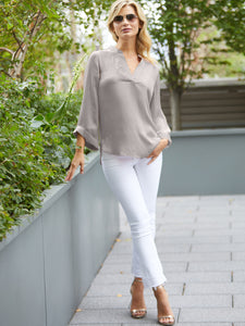 Popover styled machine washable silk charmeuse with stand collar, split neck, 3 quarter length kimono sleeves and high-low hem and side vents.  Model full frontal shot, light gray color top.