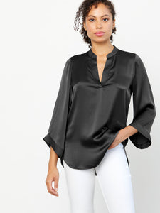 Popover styled machine washable silk charmeuse with stand collar, split neck, 3 quarter length kimono sleeves and high-low hem and side vents.  Model half frontal shot, black color top.