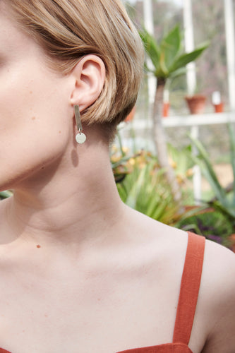 Sustainable Dot earrings. Minimalistic one long square silver sheet with a dangling circle. All handmade in Scandinavia