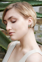 Model in green house wearing sustainable Ear-ringrings handmade in recycled sterling silver and gold