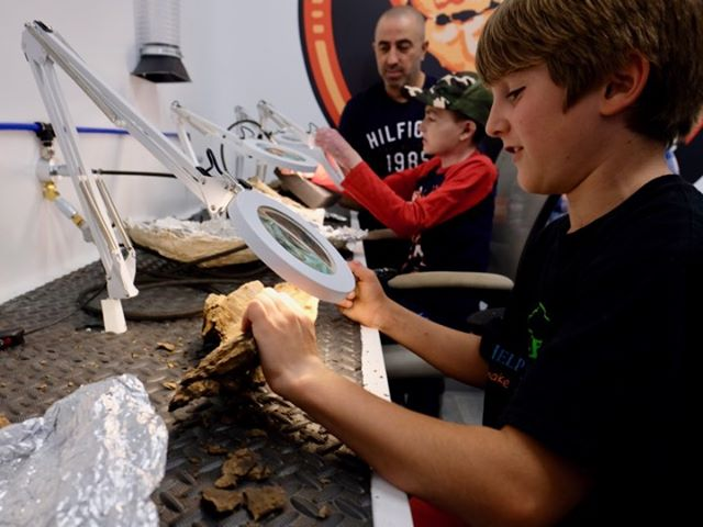 Fossil Prep in Action  Some of our junior VIP guests from the Help Fill A Dream Foundation working on triceratops bones.