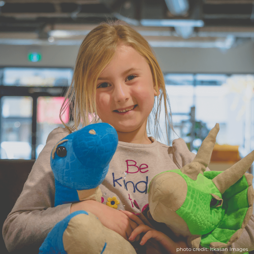 Image of a young, smiling girl with dinosaur stuffed animals. Book your next birthday party with Dino Lab Inc!
