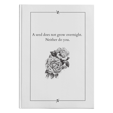 white journal with black and white flower beneath text reading a seed does not grow overnight. neither do you