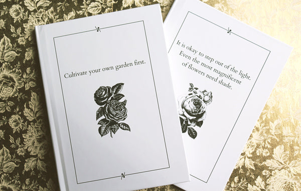 black and white journals with inspirational messages and floral motifs against gold floral background