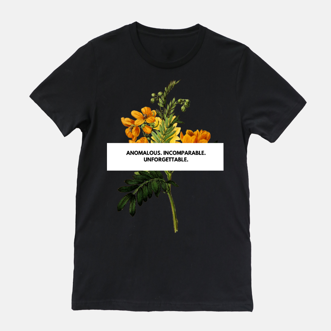"Black shirt with floral design. phrase says ""anomalous. incomparable. unforgettable."""