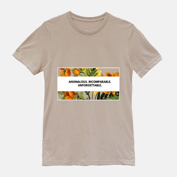 "Tan shirt with floral design. phrase says ""anomalous. incomparable. unforgettable."""