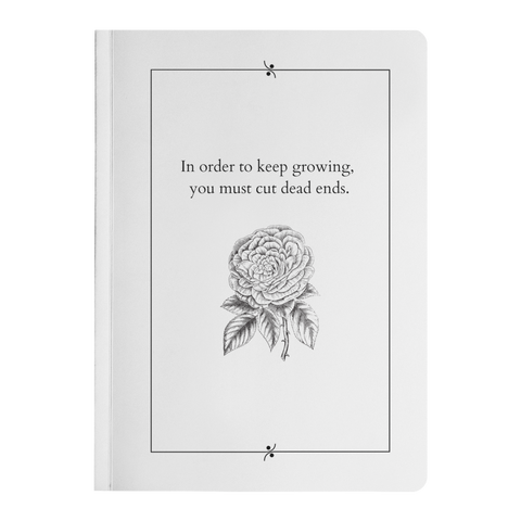 white journal with black and white flower beneath text reading in order to keep growing you must cut dead ends