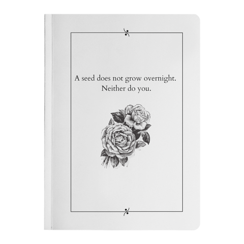 White journal with flowers beneath black text reading a seed does not grow overnight. neither do you