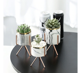 1 set of 3 marble glazed planter pots with gold iron stands in different sizes placed on a black table