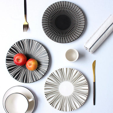 2 PLATES FROM THE DEJAVU DINNERWARE COLLECTION PLACED ON A TABLE SETTING