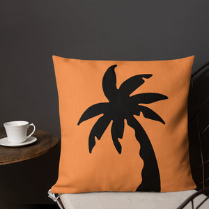 orange colour cushion cover with a black palm tree print placed on a chair