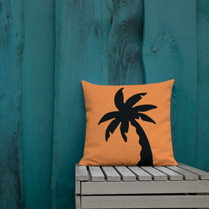 orange colour cushion cover with a black palm tree print placed outside a blue wooden wall