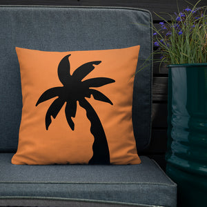 orange colour cushion cover with a black palm tree print placed on a couch FunkChez
