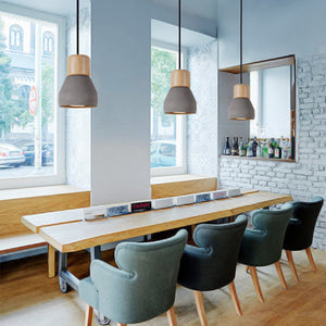 3 amara pendant lights in grey and wood finish set in a dining room