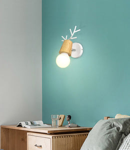 Ahorn wall lamp with white base fixed on a teal wall over a desk