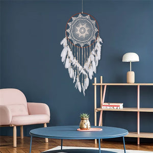 White dreamcatcher hanging on a blue wall in a living room