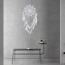 Load image into Gallery viewer, white dreamcatcher hanging on a grey wall over a table
