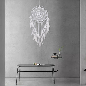 white dreamcatcher hanging on a grey wall over a table