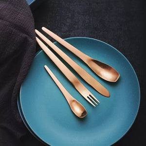 4 piece cutlery set in ombre colour placed on a blue plate
