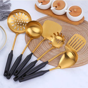 6 black and gold utensils set on a placemat near cups of tea, sugar and milk