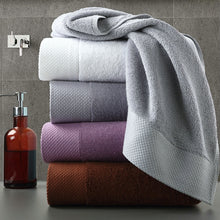 Load image into Gallery viewer, set of 4 luxury towels stacked near a hand wash on a vanity counter