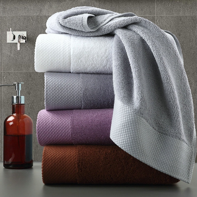 set of 4 luxury towels stacked near a hand wash on a vanity counter