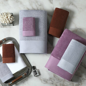 set of luxury towels in different sizes and colours of grey, rust brown and lilac stacked