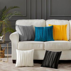 5 cushions in grey, blue, mustard yellow, ivory and black placed on a couch