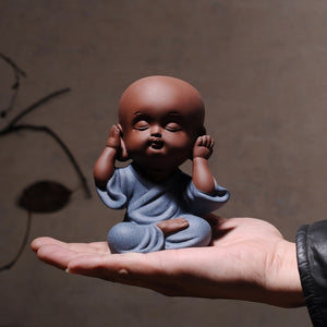hand holding a baby figurine expressing hear no evil