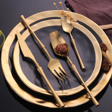 Load image into Gallery viewer, GOLD PLATED ROYALTY CUTLERY SET SITTING ON TOP OF A BLACK PLATE WITH GOLD TRIMMED EDGES