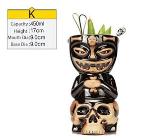 black and cream ceramic tiki tumbler in the shape of a skull filled with cocktail and some veggies with size specs