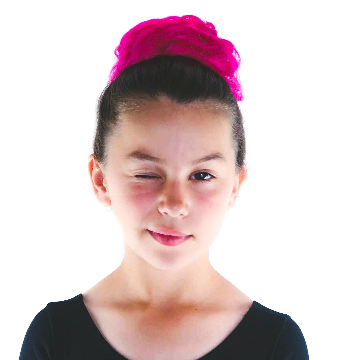 Ballerina hairstyle on a young girl with a hot pink curly ballet bun style