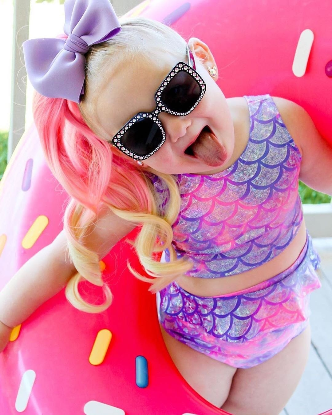 Young girl modeling her Cupcake Maggic Tail ponytail extension in bright pink and blonde