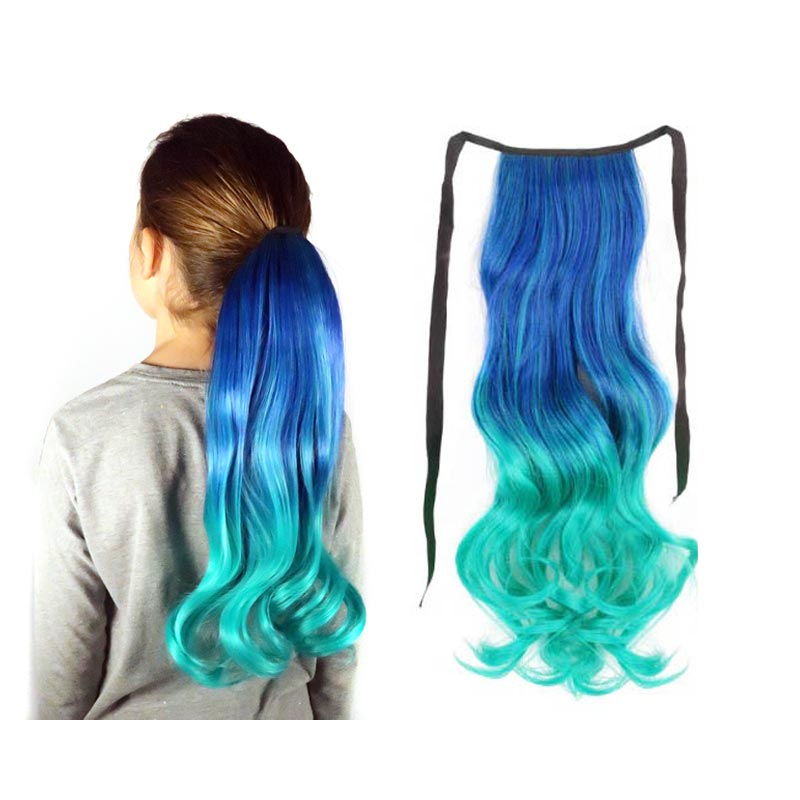 A young model wears a teal blue, green and aqua ombre hair extension ponytail