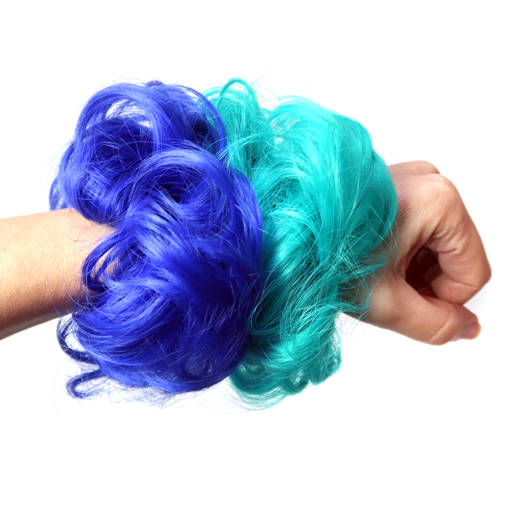 Hair scrunchies with curly fluffy blue and green hair on a wrist.