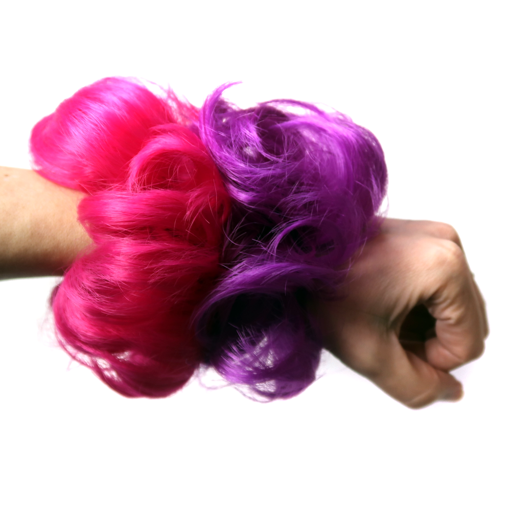 Hair scrunchies hair pieces in hot pink and purple worn on a wrist like a hair band
