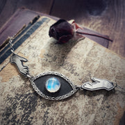 Hands reaching for moonstone eye necklace