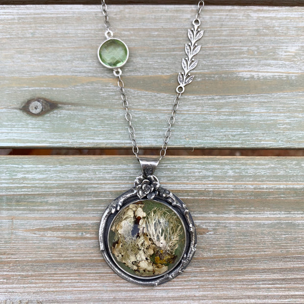 Silver nature necklace with lichen terrarium, green amethyst, silver vines, succulent, and twig
