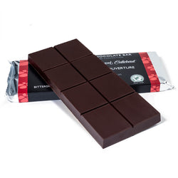 Bitter sweet chocolate baking bar propped up on to a packaged baking bar
