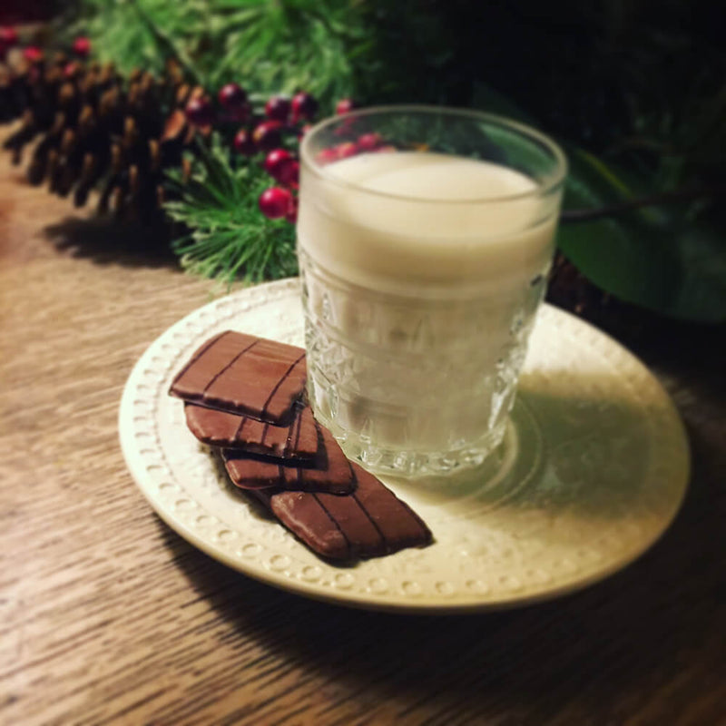 Four milk chocolate covered almonds biscuits and a glass of milk on a white plate with christmas greenery in background
