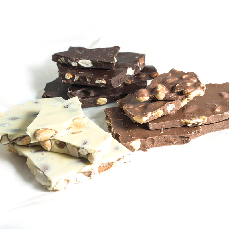 Three stacks of nut bark, dark, milk and white chocolate