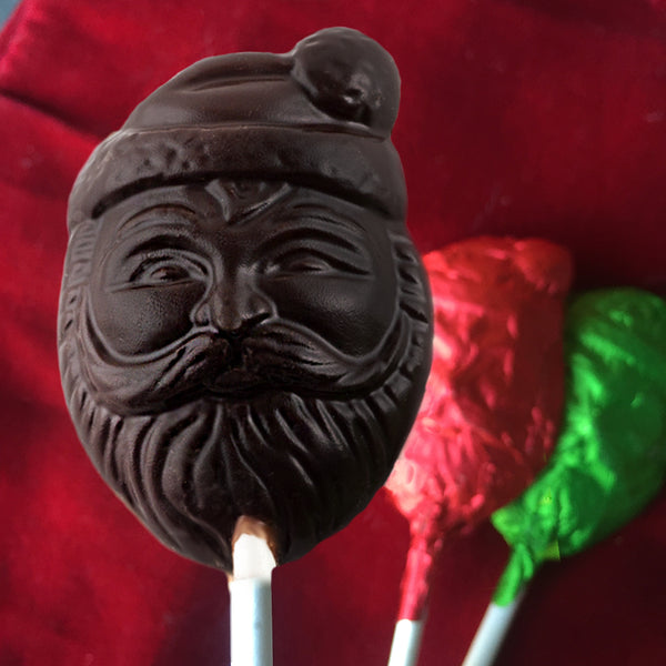 One dark chocolate lollipop with two lollipops with red and green foil on a red background