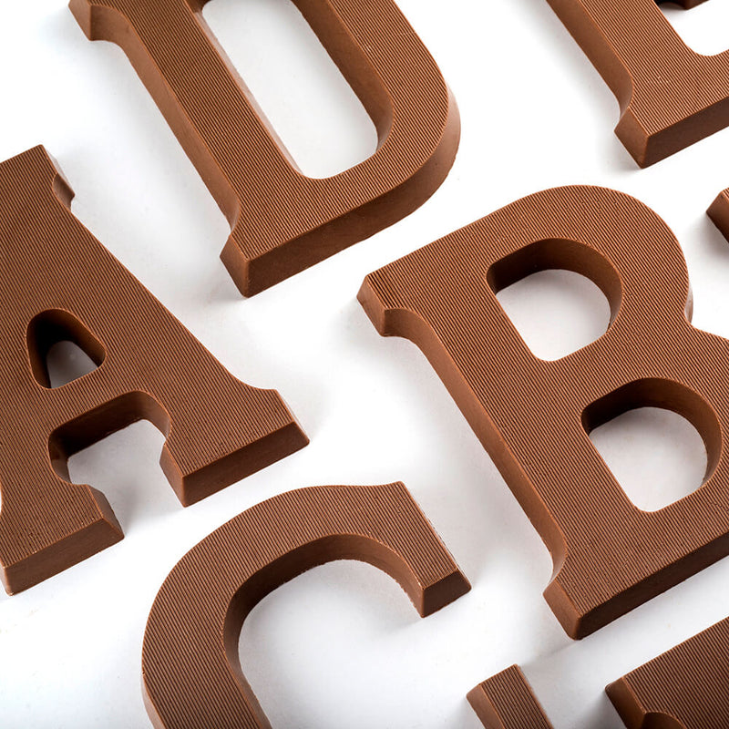 Overhead view of portions of milk chocolate letters A, B, C, D