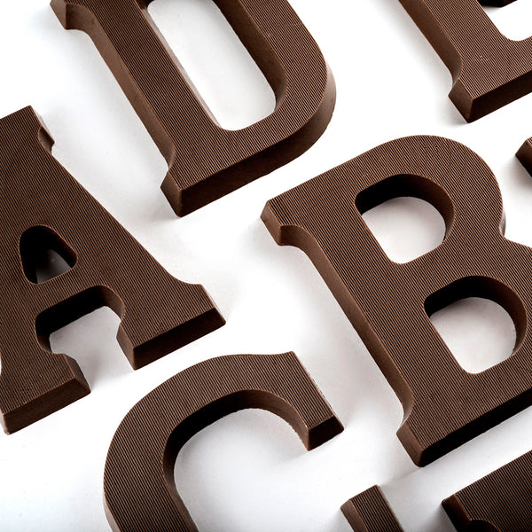 Overhead view of portions of dark chocolate letters A, B, C, D